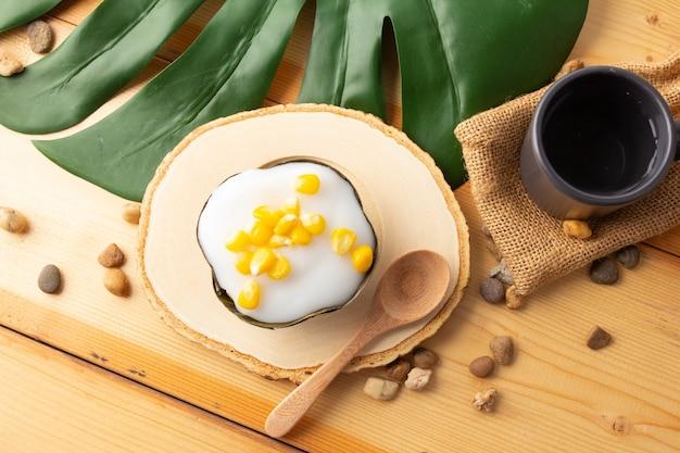 とうもろこし入りタイプディングココナッツトップ、バナナの葉で包んだデザート。タイ人は「カノムタコ」と呼んでいます。木製の受け皿と木のスプーンにとうもろこしを乗せたタコ、上面図。