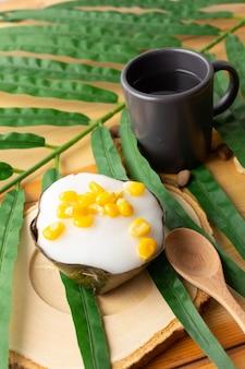 とうもろこし入りタイプディングココナッツトップ、バナナの葉で包んだデザート。タイ人は「カノムタコ」と呼んでいます。とうもろこしを木製の受け皿とスプーンに乗せたタコと、黒いガラスのお茶。