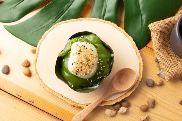 新鮮なパンダナスを添えたタイのプディングココナッツトップ、バナナの葉で包んだデザート。タイの人々は「カノムタコ」と呼びます。木製の受け皿と木のスプーンの上にイチョウを置いたタコ、上面図。