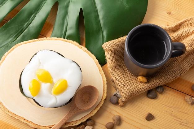 イチョウの種をまぶしたタイのプディングココナッツトップ、バナナの葉で包んだデザート。タイの人々は「カノムタコ」と呼んでいます。イチョウを木製の受け皿と木のスプーンの上に置いたタコ、上面図。