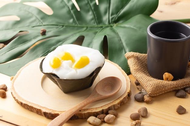 タイプディングココナッツトップにイチョウの種、デザートをバナナの葉で包んだもの。タイ人は「カノムタコ」と呼んでいます。イチョウを木製の受け皿とスプーンに乗せたタコと、黒いガラスのお茶。