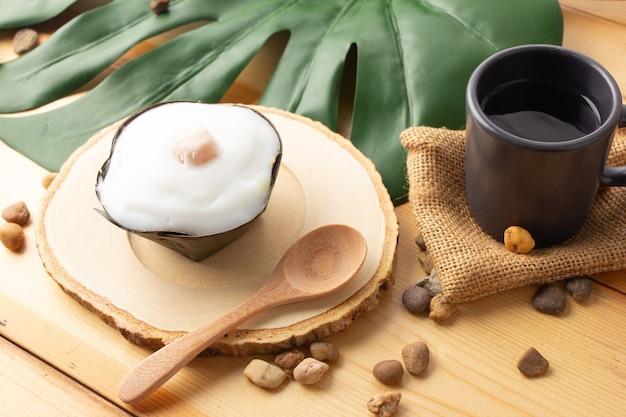 タイのプディングタロイモのココナッツトップ、バナナの葉で包んだデザート。タイの人々は「カノムタコ」と呼びます。タロイモを木製の受け皿と木のスプーンに置いたタコ、上面図。