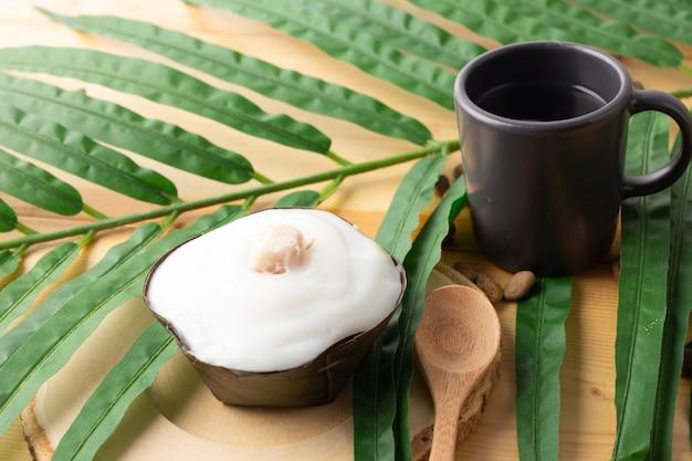 タイのプディングココナッツトップにタロイモ、デザートをバナナの葉で包んだもの。タイの人々は「カノムタコ」と呼んでいます。タロイモを木製の受け皿とスプーンに乗せたタコ。