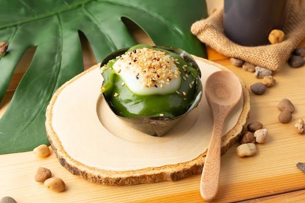 新鮮なパンダナスのトップにゴマを添えたタイプディングココナッツ、バナナの葉で包んだデザート。タイの人々は「カノムタコ」と呼んでいます。タコは木製の受け皿と木のスプーンの上に置かれ、黒いガラスにお茶が入っています。