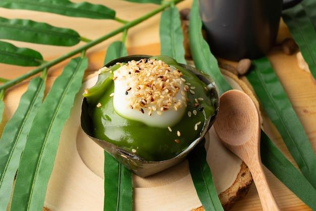 新鮮なパンダナスのトップにゴマを添えたタイのプディングココナッツ、バナナの葉で包んだデザート。タイの人々は「カノムタコ」と呼びます。タコは木製の受け皿と木のスプーンの上に置かれます。