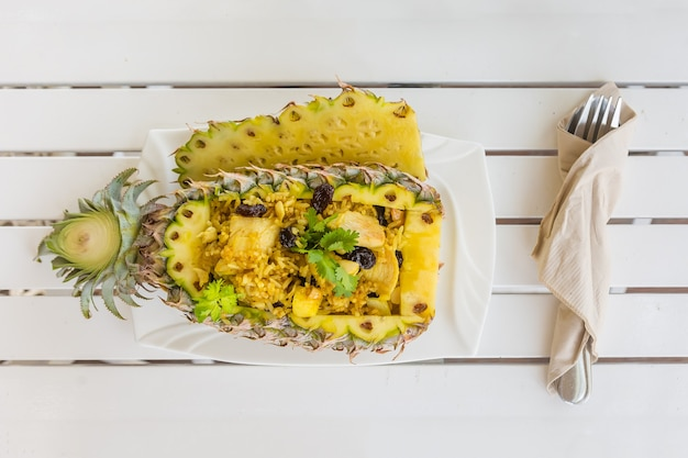 Thai rice with chicken in pineapple plate with vegetables on the wooden table fork and knife