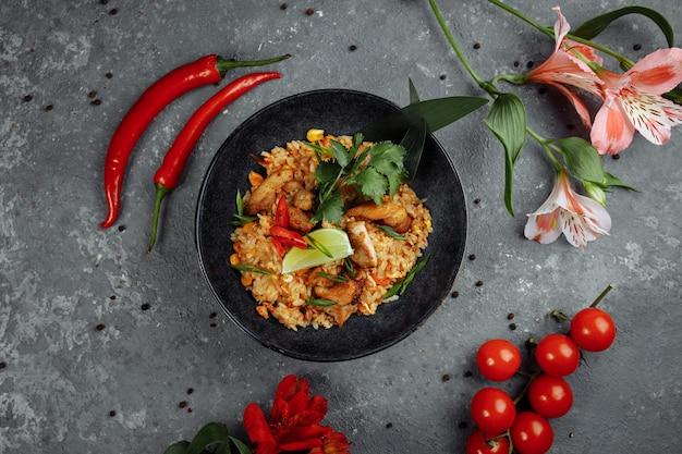 Тайский рис с курицей. тайское блюдо из риса, курицы, ялтинского лука, кукурузы, ананаса, помидоров, соевого соуса, пасты чили, кинзы, лайма, перца чили, зеленого лука, специй