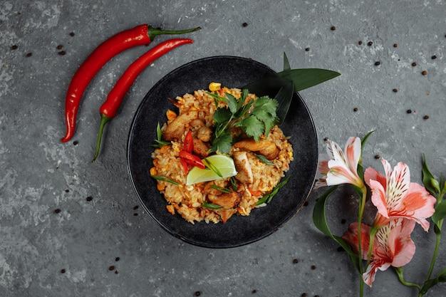 Тайский рис с курицей. тайское блюдо из риса, курицы, ялтинского лука, кукурузы, ананаса, помидоров, соевого соуса, чили-пасты, кинзы, лайма, перца чили