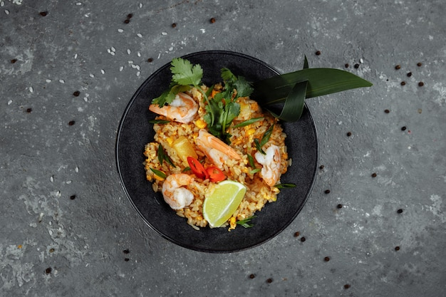 Thai rice with shrimp in a black plate on a dark background. copyright place