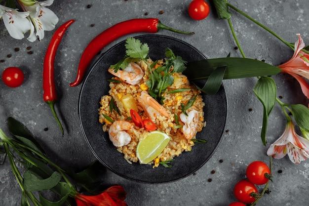 Тайский рис с креветками в черной тарелке на темном фоне. авторское место.