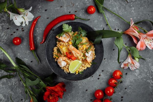 Тайский рис с креветками в черной тарелке на темном фоне. место авторского права