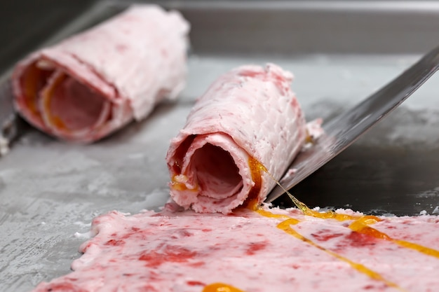 Thai roll ice cream is made by hand on the freezer. sweet dessert made from natural berries and ingredients. the process of making food.