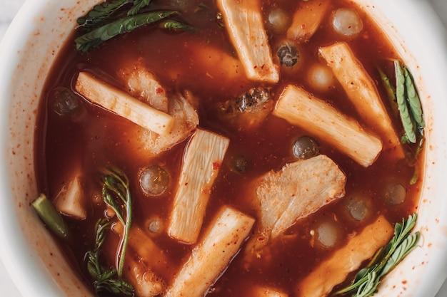 Тайский кислый суп из икры рюкю подается в белой миске