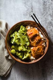 Блюдо из тайского лосося в кокосовом соусе со свежей брокколи и рисом в глиняной миске с палочками для еды