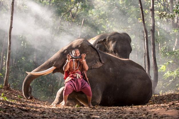 象とジャングルの中でタイの羊飼い。タイ文化からの歴史的なライフスタイルの瞬間