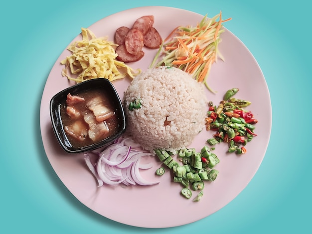 Thai shrimp paste fried rice with sweet pork and other seasoning ingredients isolated on blue