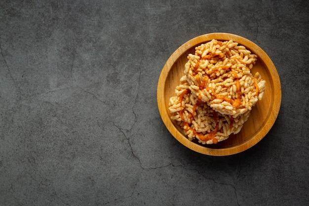 Spuntino tailandese; kao tan o cracker di riso in ciotola di legno