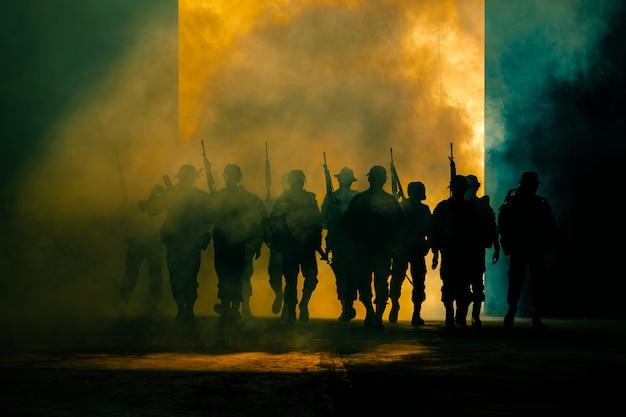 Тайская солдатская команда спецназа в полной униформе шагает сквозь дым и держит пистолет под рукой