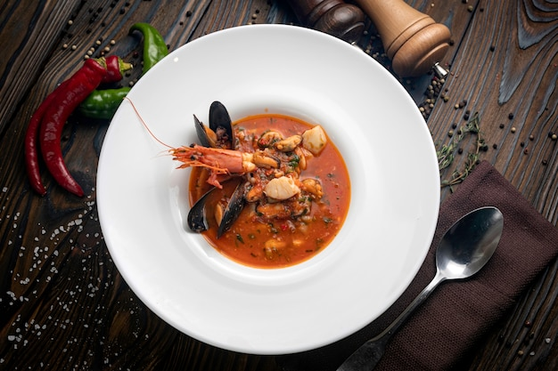 Thai soup with seafood in a white plate on a wooden background