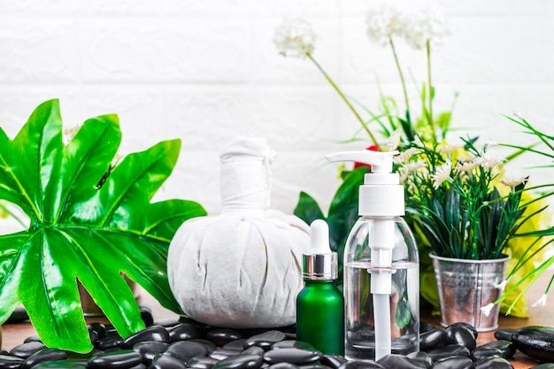 Thai spa massage setting with serum oil bottle dropper mock up or essential oil and thai herbal compress balls on black stone against green leave background
