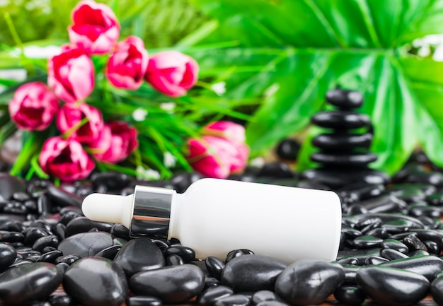 Thai spa massage setting with serum oil whire bottle dropper mock up or essential oil on black stone against green leave background
