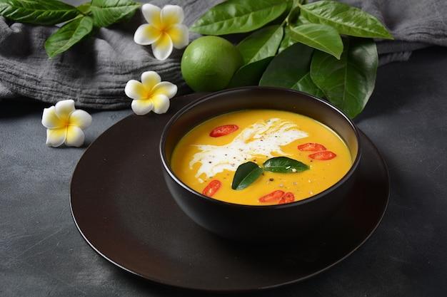 カフィアライムの葉、赤唐辛子、ガランガルルーツパウダーを使ったタイのスパイシーなカボチャとココナッツミルクのスープ。