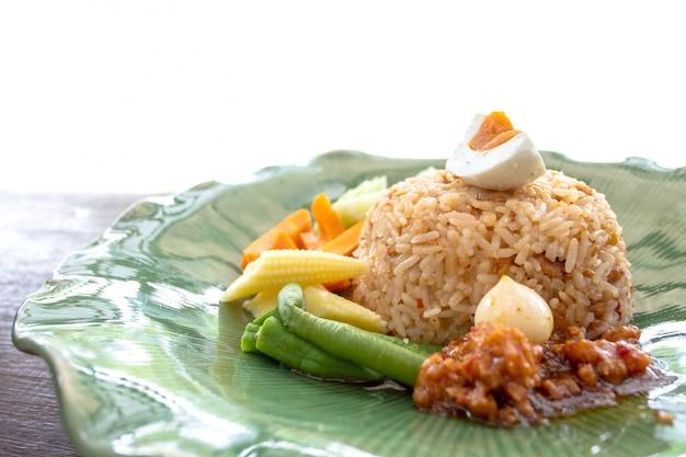 タイ風スパイシーなエビのペーストソースチャーハンと揚げ魚の豚肉の木製テーブル