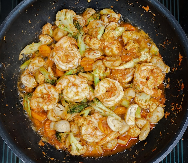 Thai spicy stir fried vegetables and shrimps with spicy red curry paste on a pan