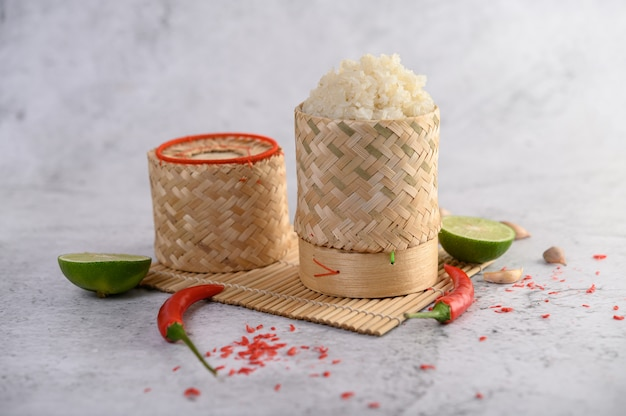 Thai sticky rice in a woven bamboo basket on a wooden panel with chilies, lime, and garlic