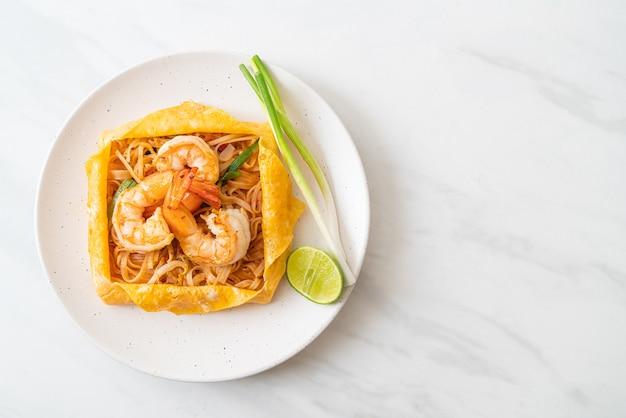 エビと卵のラップが付いたタイの炒め麺(パッタイ)。タイ料理のスタイル