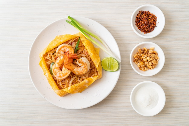 Thai stir fried noodles with shrimps and egg wrap (pad thai)