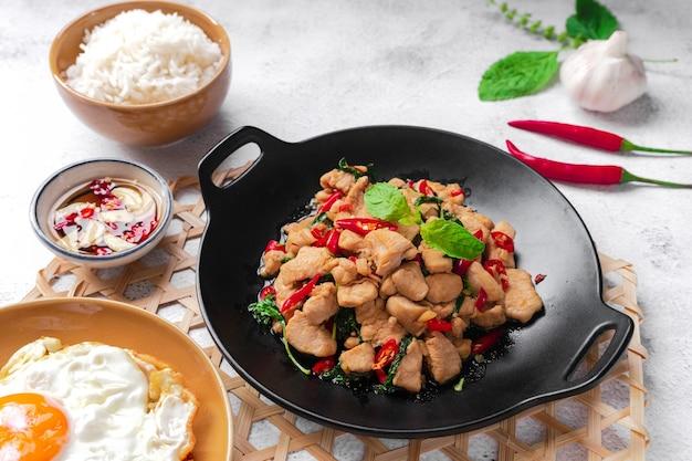 タイのストリート フード バジル フライド チキンと目玉焼きを添えて、白い表面にご飯と魚醤のボウル