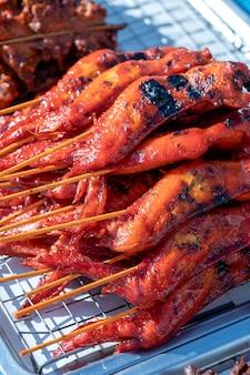 태국 노점상이 태국 코팡안 섬의 길거리 음식 시장에서 구운 닭고기를 판매합니다. 확대