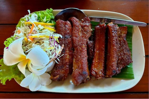 나무 테이블에 흰색 접시에 야채와 함께 태국 스타일 바베큐 갈비 돼지 고기