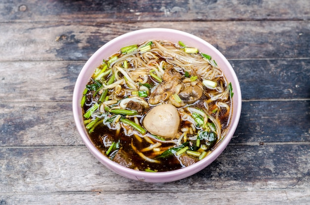 Thai style beef noodle on wooden table