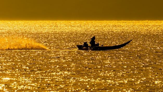オレンジ色の海の真ん中にあるタイ風ボート