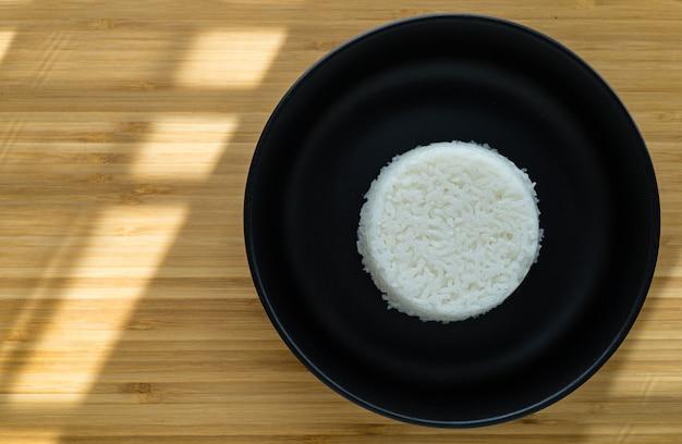 Тайский стиль приготовления парового риса положить на черную тарелку на деревянном фоне с копией пространства. угол обзора сверху.