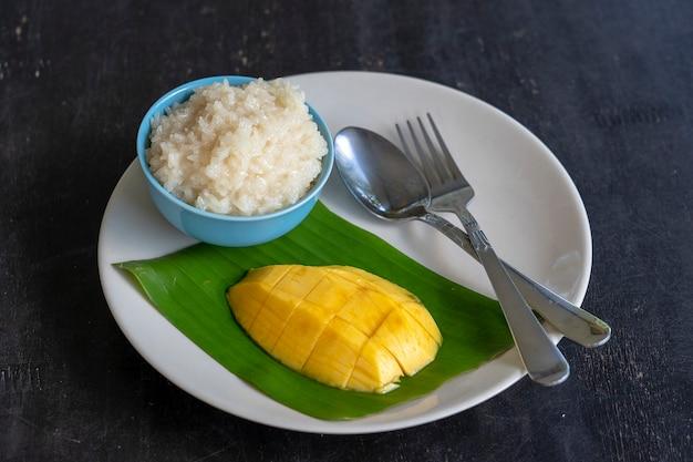 태국 스타일 디저트, 접시에 찹쌀이 든 망고. 노란색 망고와 찹쌀은 태국의 인기 있는 전통 디저트입니다. 확대