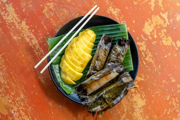 タイ風デザート、ヤシの葉にバナナもち米を添えた黄色いマンゴー。黄色いマンゴーともち米はタイの人気の伝統的なデザートです。閉じる