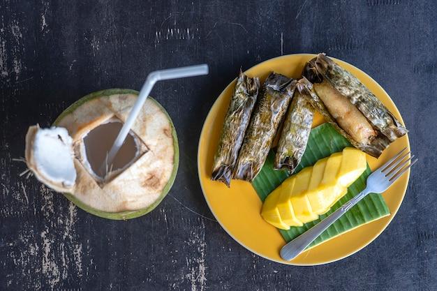 태국 스타일 디저트, 야자수 잎에 바나나 찹쌀을 넣은 노란색 망고. 노란색 망고와 찹쌀은 태국의 인기 있는 전통 디저트입니다. 확대