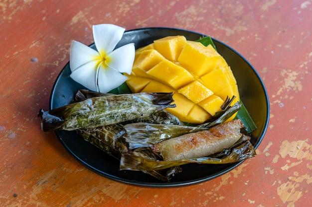Десерт в тайском стиле, желтое манго с банановым липким рисом в пальмовых листьях. желтое манго и клейкий рис - популярный традиционный десерт таиланда. закрыть вверх