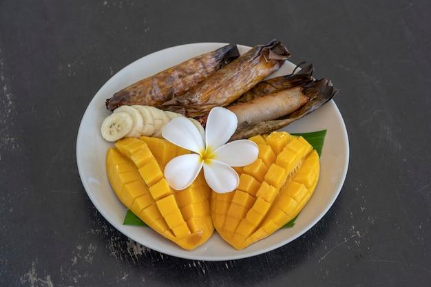 タイ風デザート、ヤシの葉にバナナもち米を添えた黄色いマンゴー。イエローマンゴーともち米はタイの人気の伝統料理です。閉じる