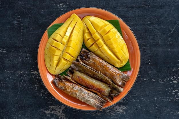 태국 스타일 디저트, 야자수 잎에 바나나 찹쌀을 넣은 노란색 망고. 노란색 망고와 찹쌀은 태국의 인기 있는 전통 음식입니다. 확대
