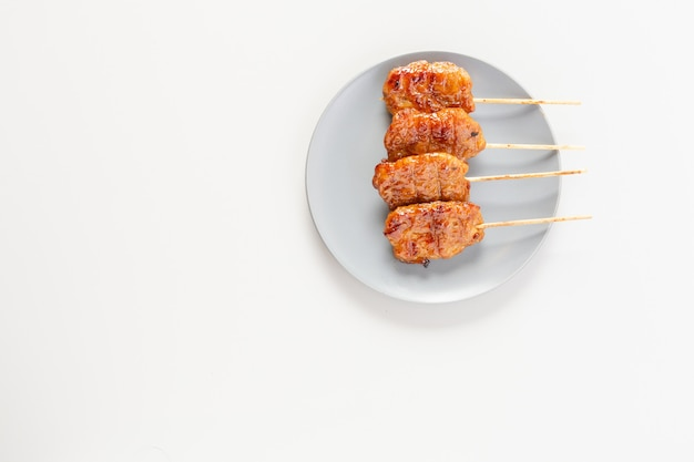 Thai-style grilled pork on a skewer placed on a plate is street food in thailand