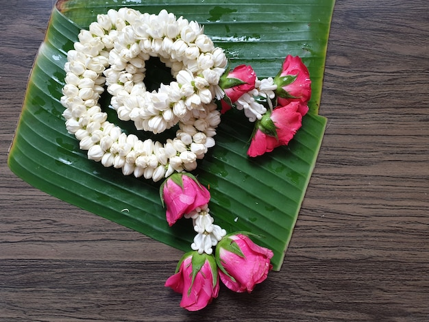 Thai style of jasmine garland on banana leaves and wooden background