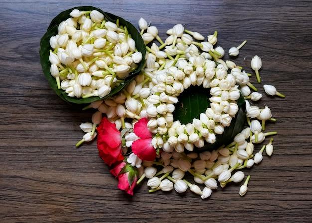 ジャスミンの花輪と木製の背景に新鮮なジャスミンの花のタイスタイル