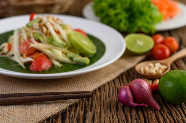 Cibo piccante in stile tailandese, concetto di cibo som tum, decorazione di oggetti di scena aglio, limone, arachidi, pomodori e scalogni sul tavolo di legno