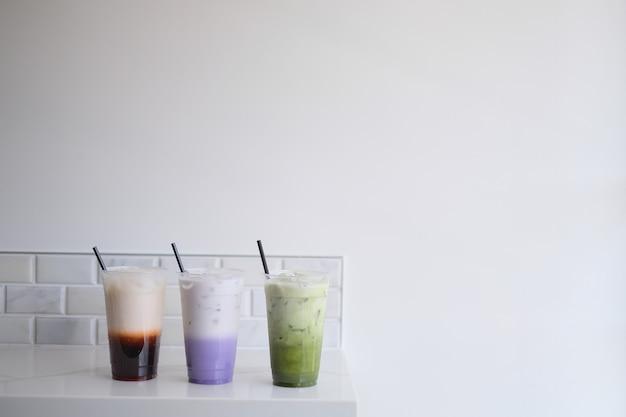 Тайский чай, чай с молоком таро, зеленый чай маття на белом фоне Premium Фотографии