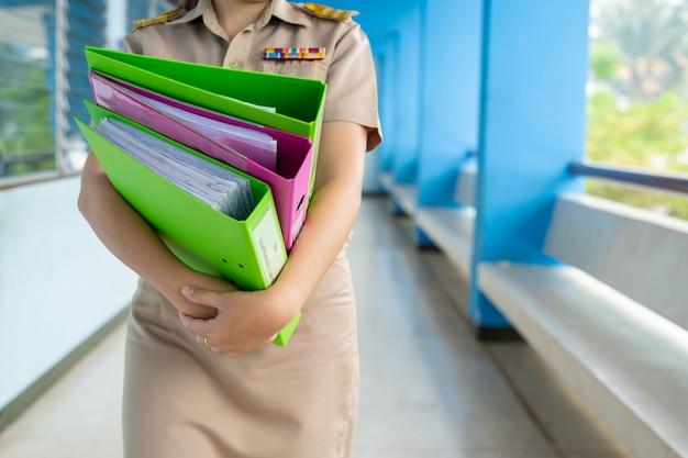 Тайский учитель в официальной одежде стоит и держит папки с файлами
