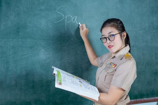 Тайский учитель в официальной одежде преподает перед щитом